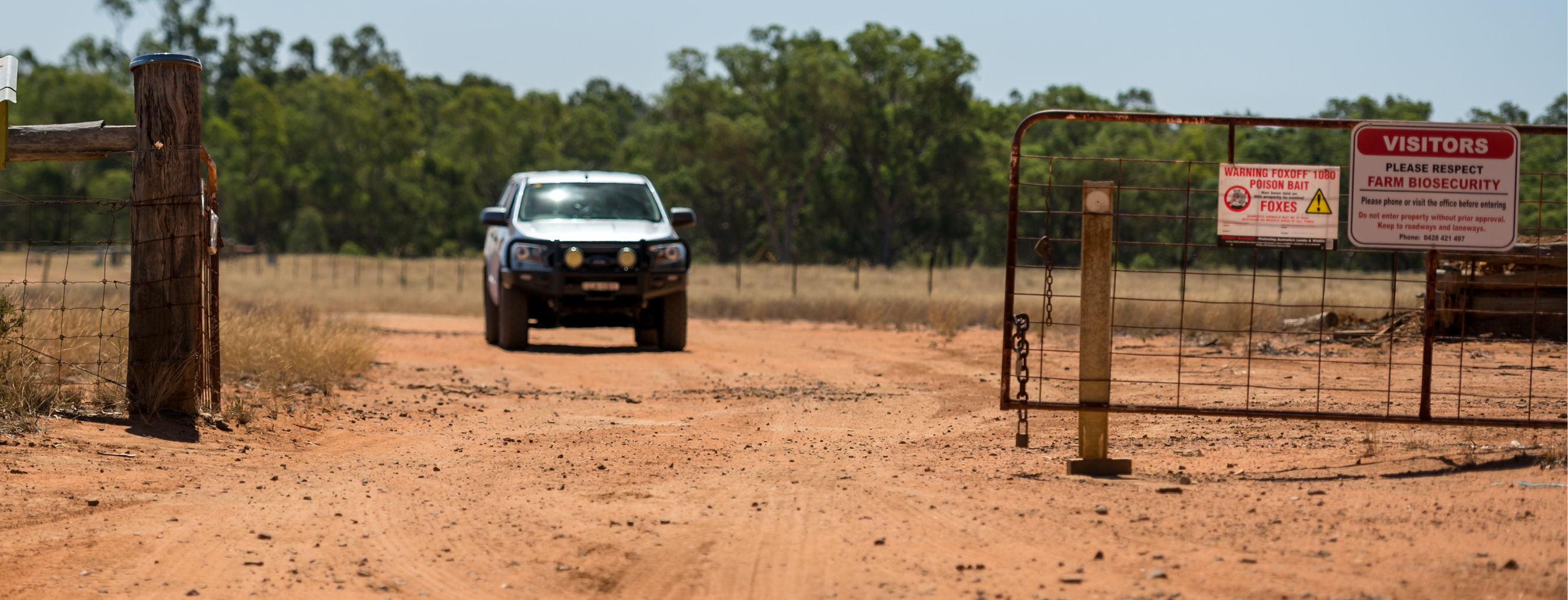Ute driving up to a farm entrance that has biosecurity signs on the fence